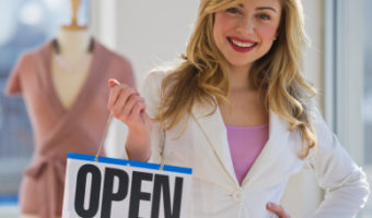 Shopkeeper holding open sign
