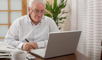 Senior man working from home with a laptop.