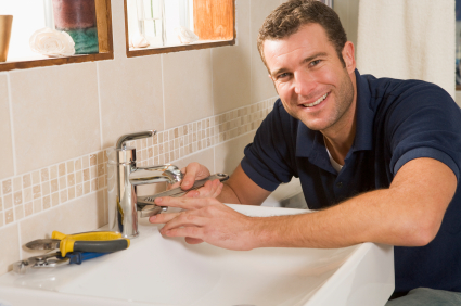 Plumber working on sink smiling