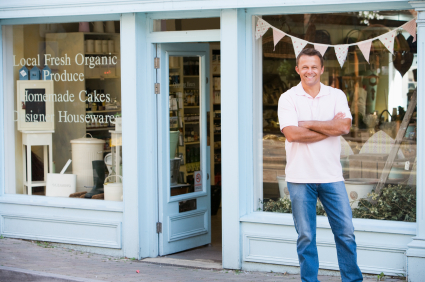 Man standing in front of organic food store smiling