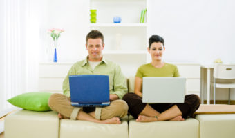 Young couple sitting on sofa, using laptops